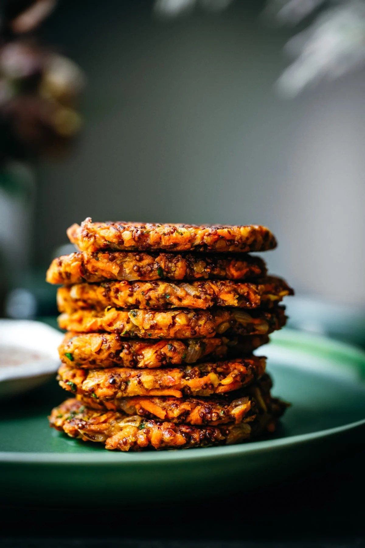 close up side view of a stack of carrot fritters on a green plate.