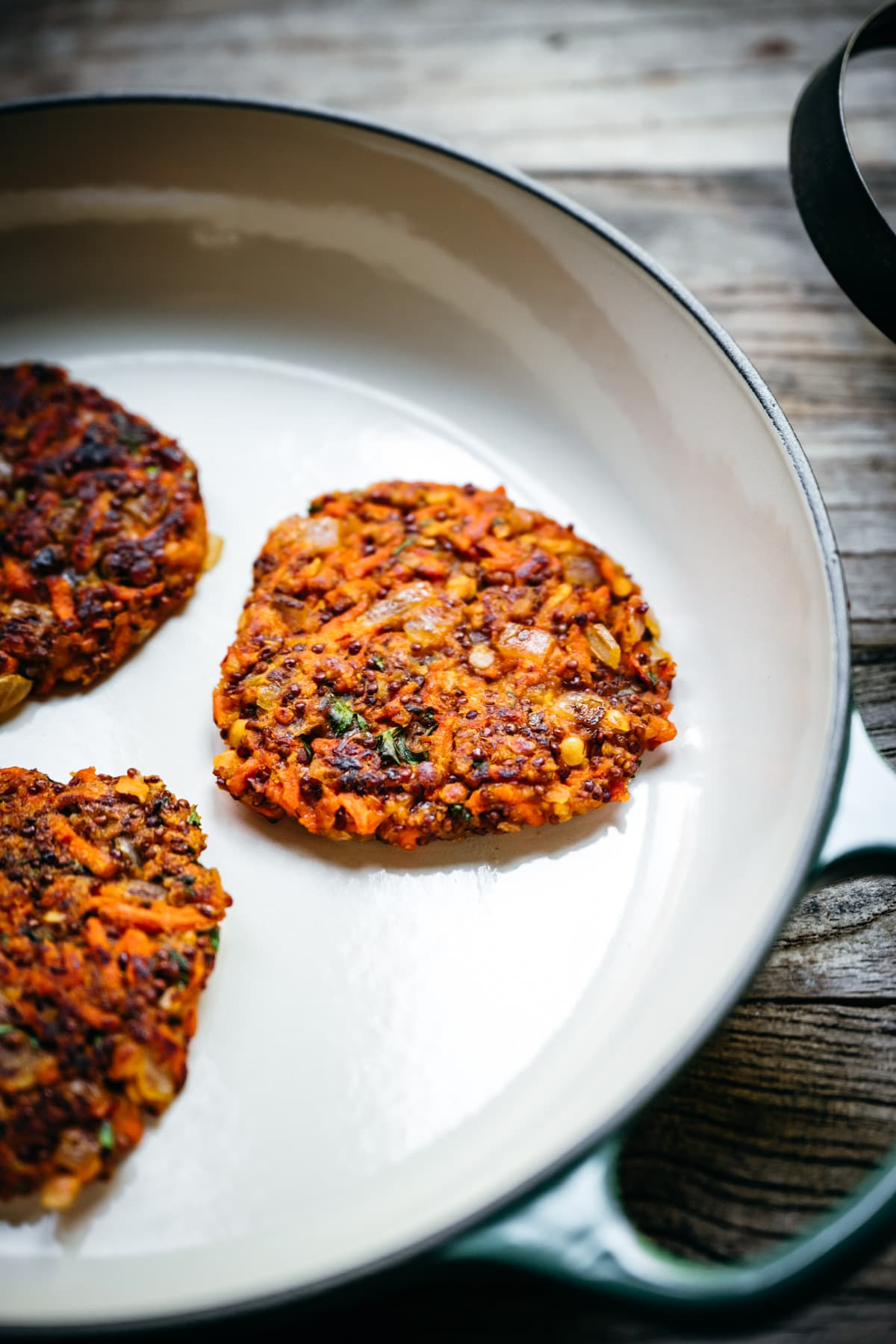 side view of carrot quinoa fritter in a pan.