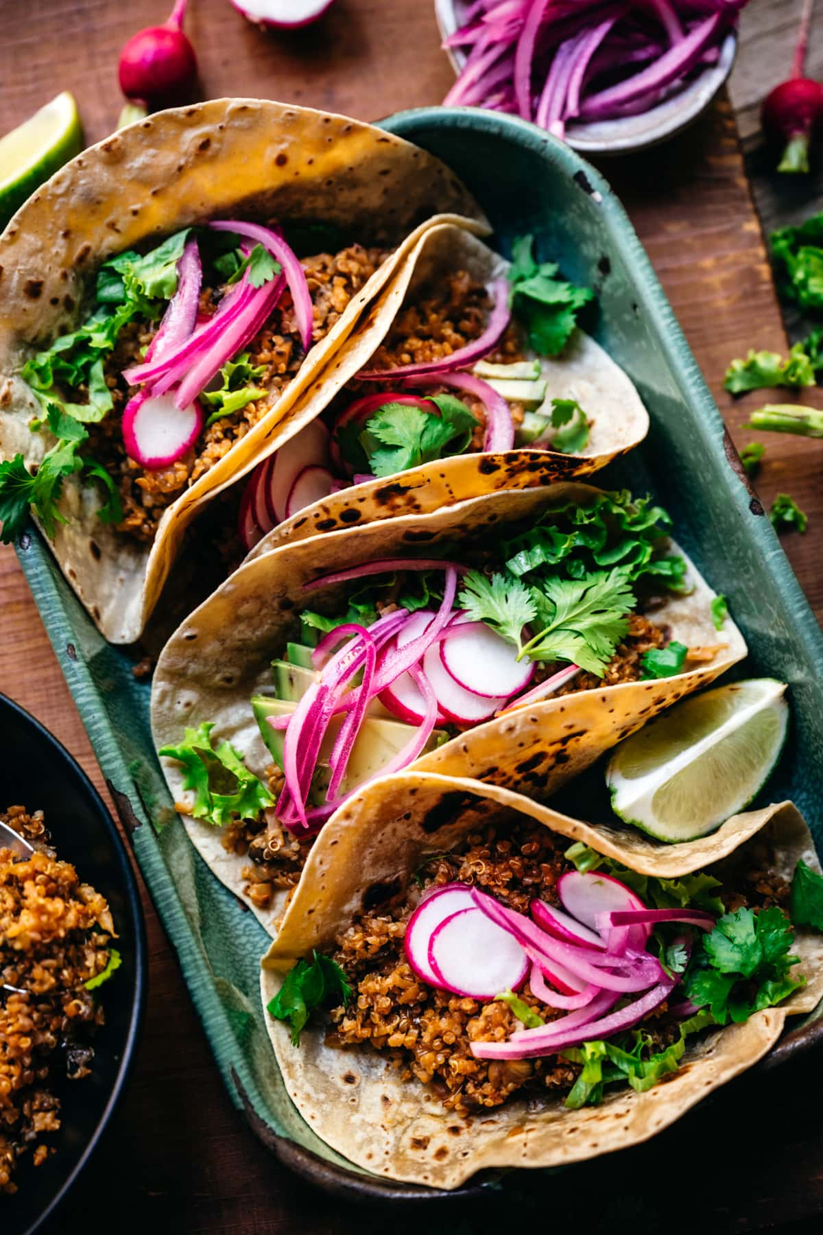 close up view of tacos with vegan cauliflower quinoa taco meat and pickled onion.
