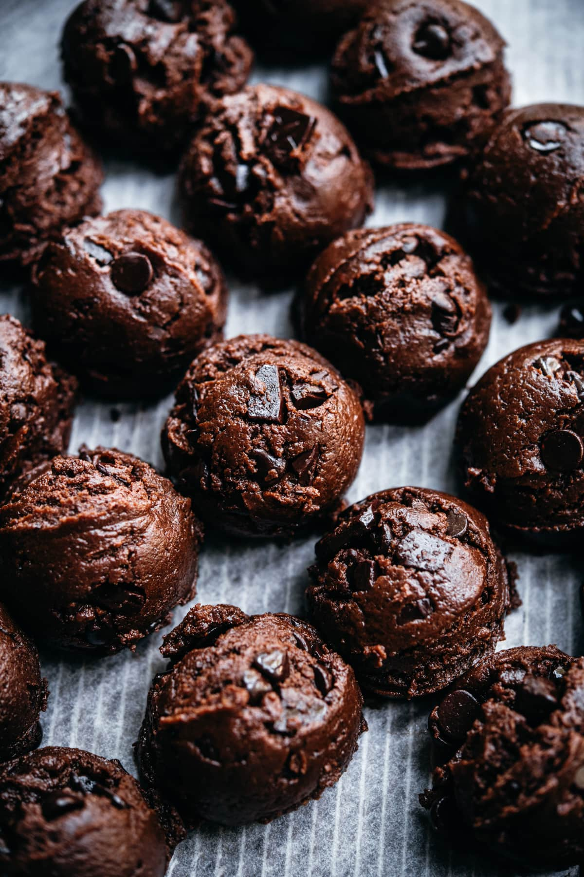 side view of chocolate cookie dough balls on parchment paper.