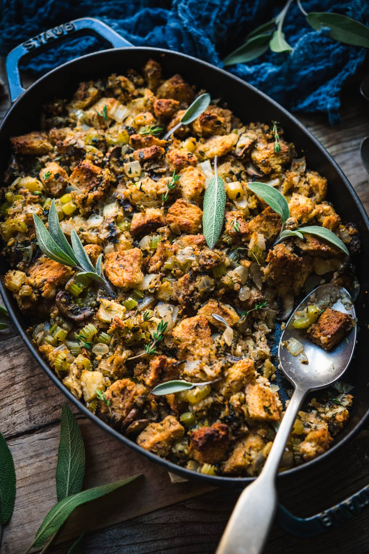 side view of gluten free vegan stuffing in an oval pan with serving spoon.