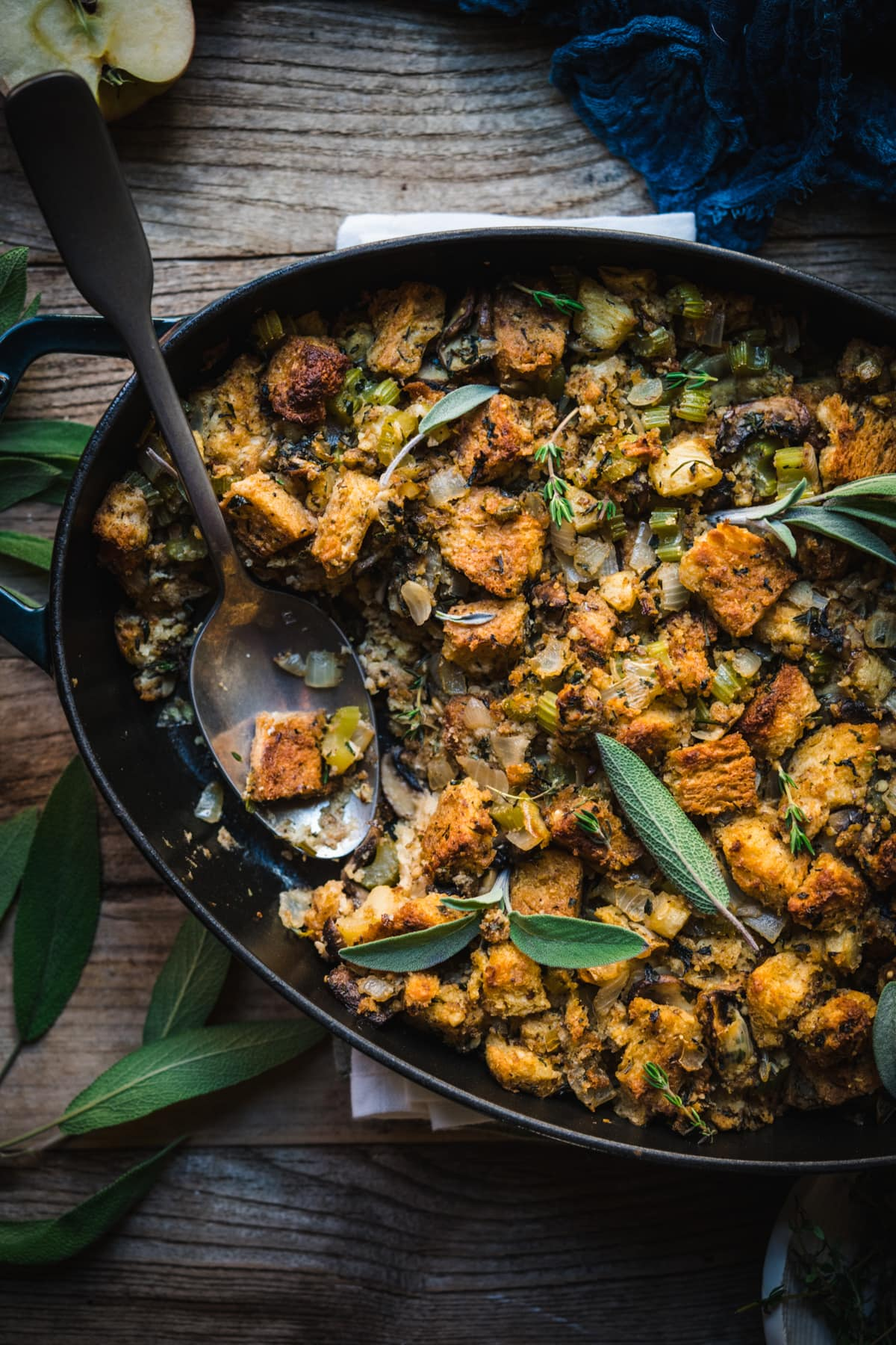 overhead view of gluten free vegan stuffing in an oval pan with serving spoon.