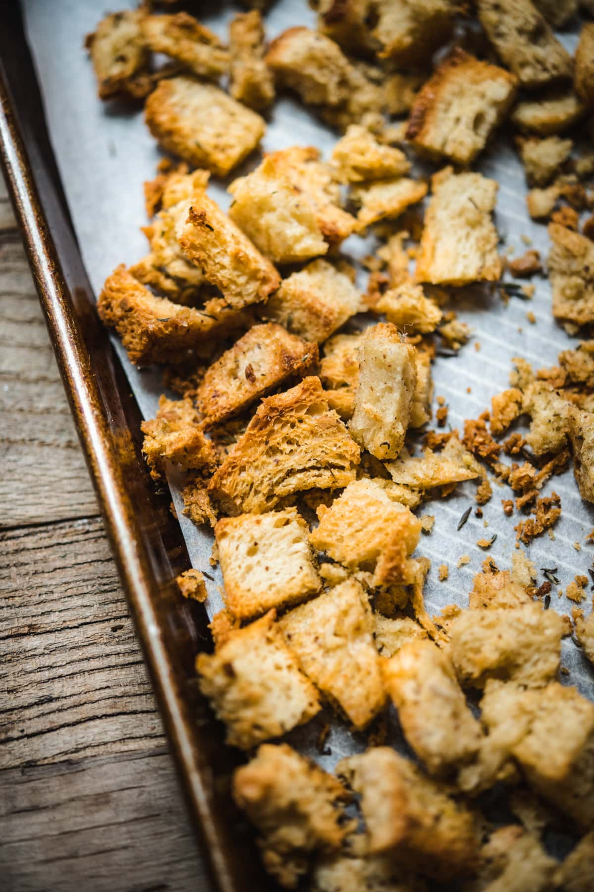 close up view of toasted bread cubes on a sheet pan.
