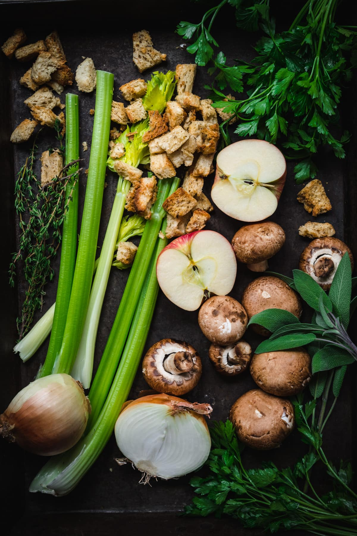 overhead view of ingredients for stuffing on a baking sheet, including celery, apple, mushrooms, onions and toasted bread.