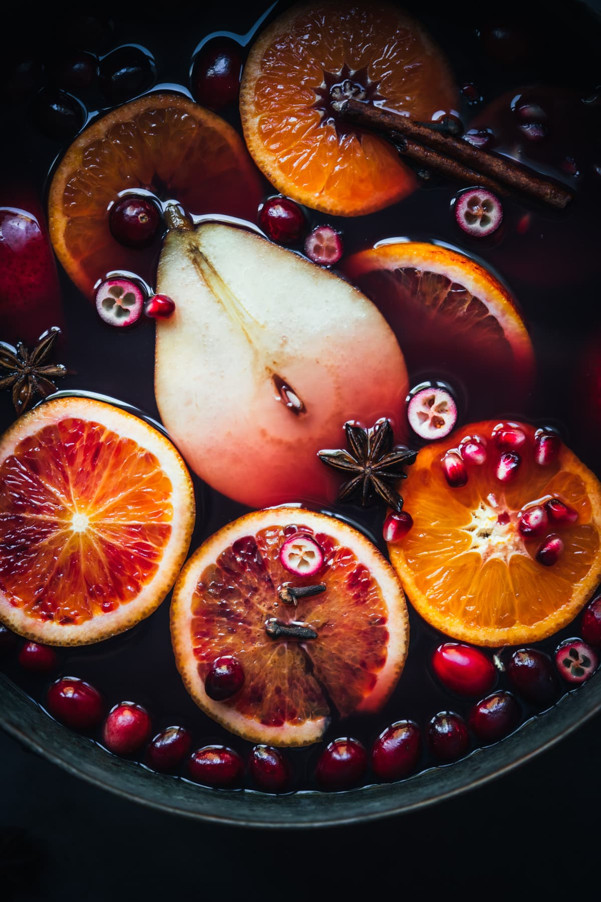 close up view of fruits and spices in mulled wine in pot.