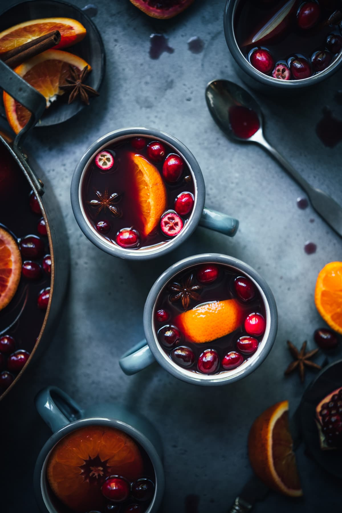 overhead view of homemade citrus mulled wine in grey mugs garnished with cranberries and orange slices.