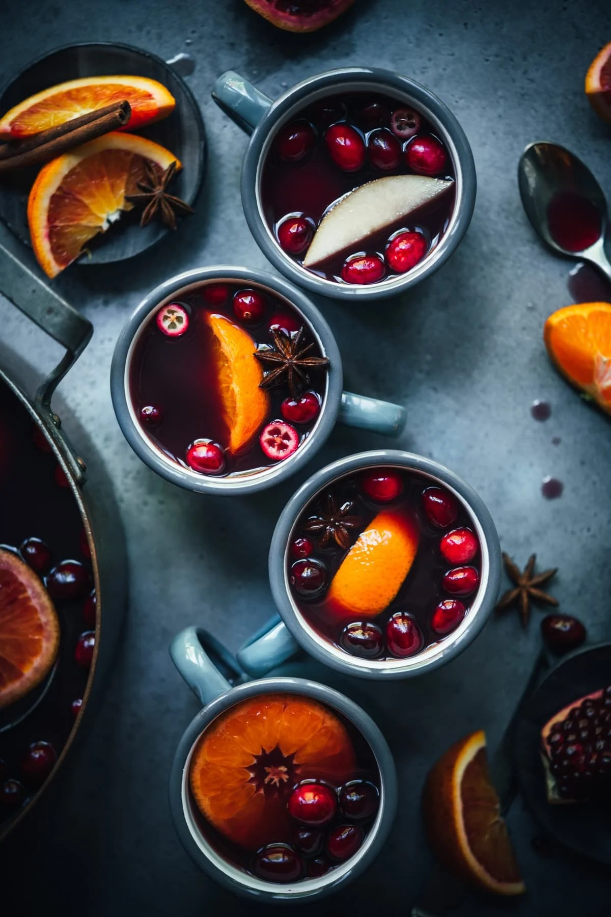 overhead view of homemade citrus mulled wine in grey mugs garnished with cranberries, star anise and orange slices.