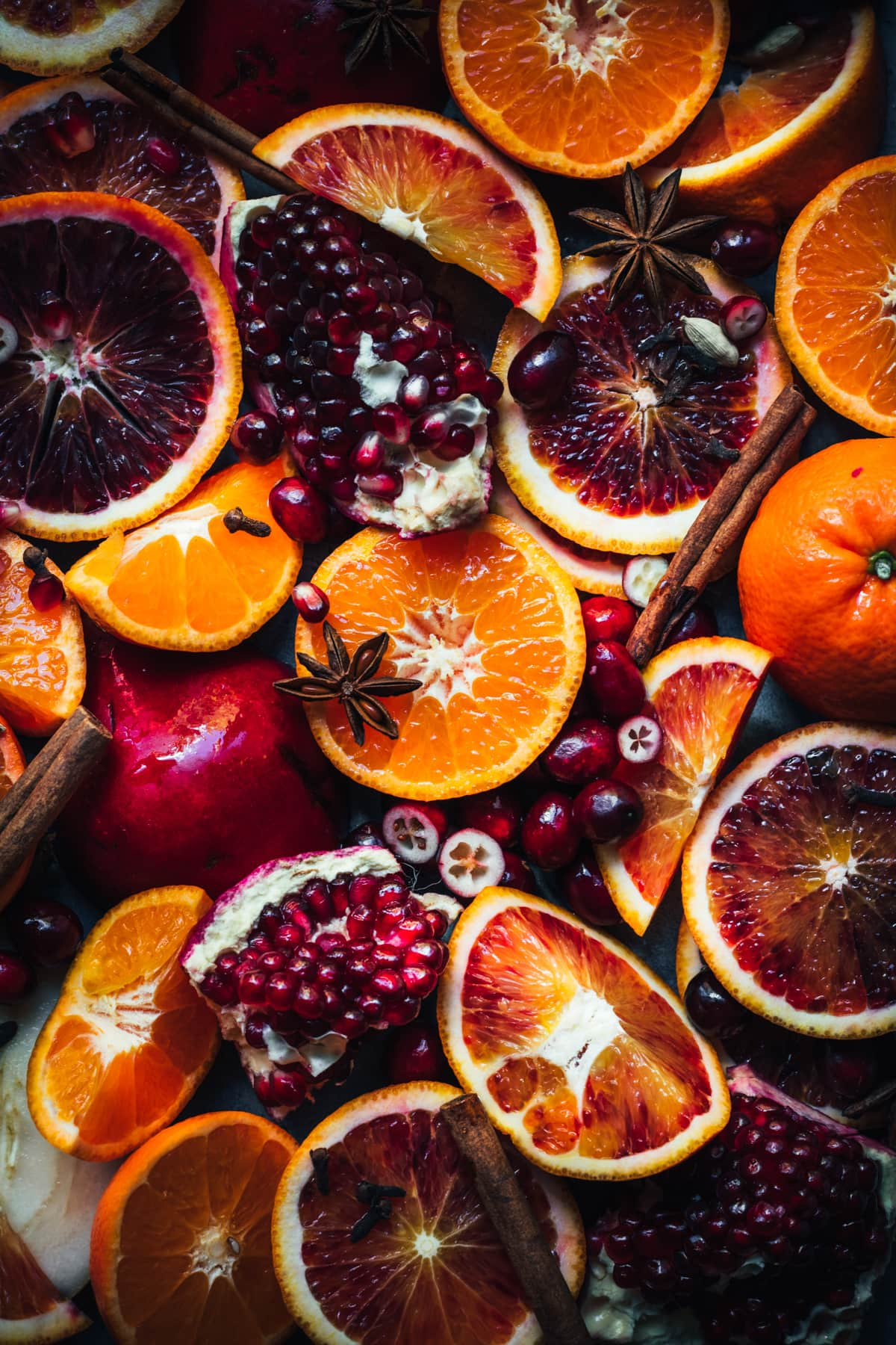 close up overhead view of ingredients for mulled wine, including citrus slices, pomegranate, cranberries and whole spices.
