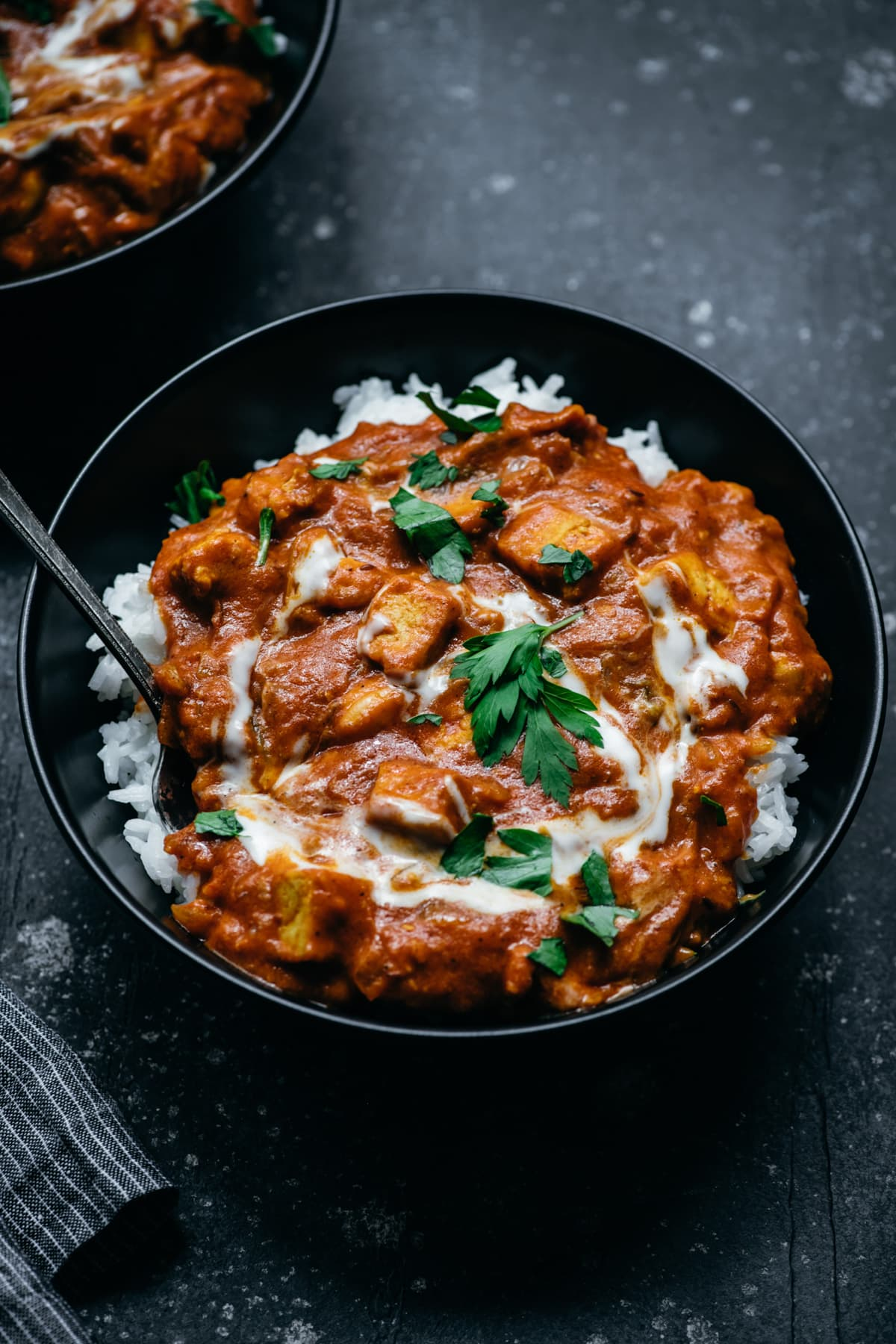 side view of vegan tofu tikka masala in a bowl with white rice.