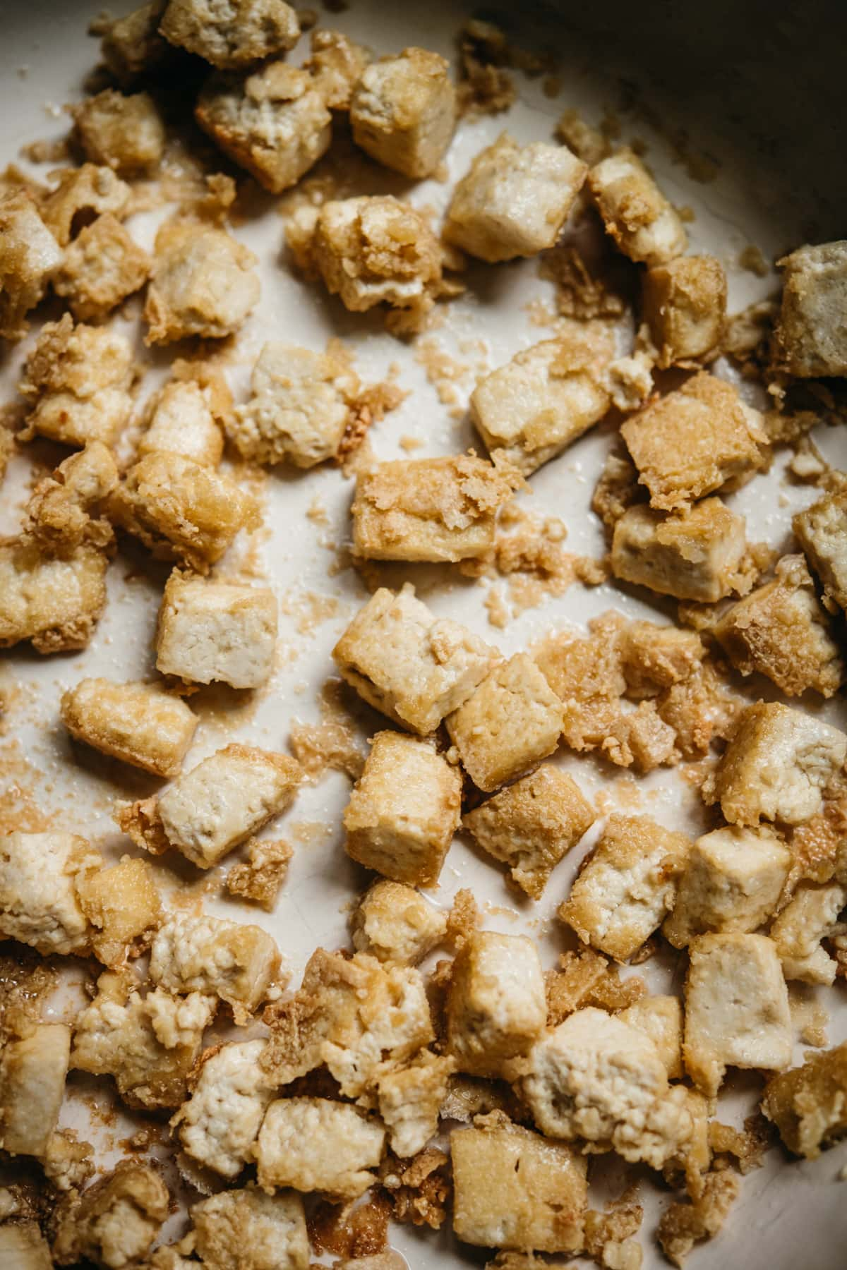close up view of crispy pan-fried tofu in a pan.