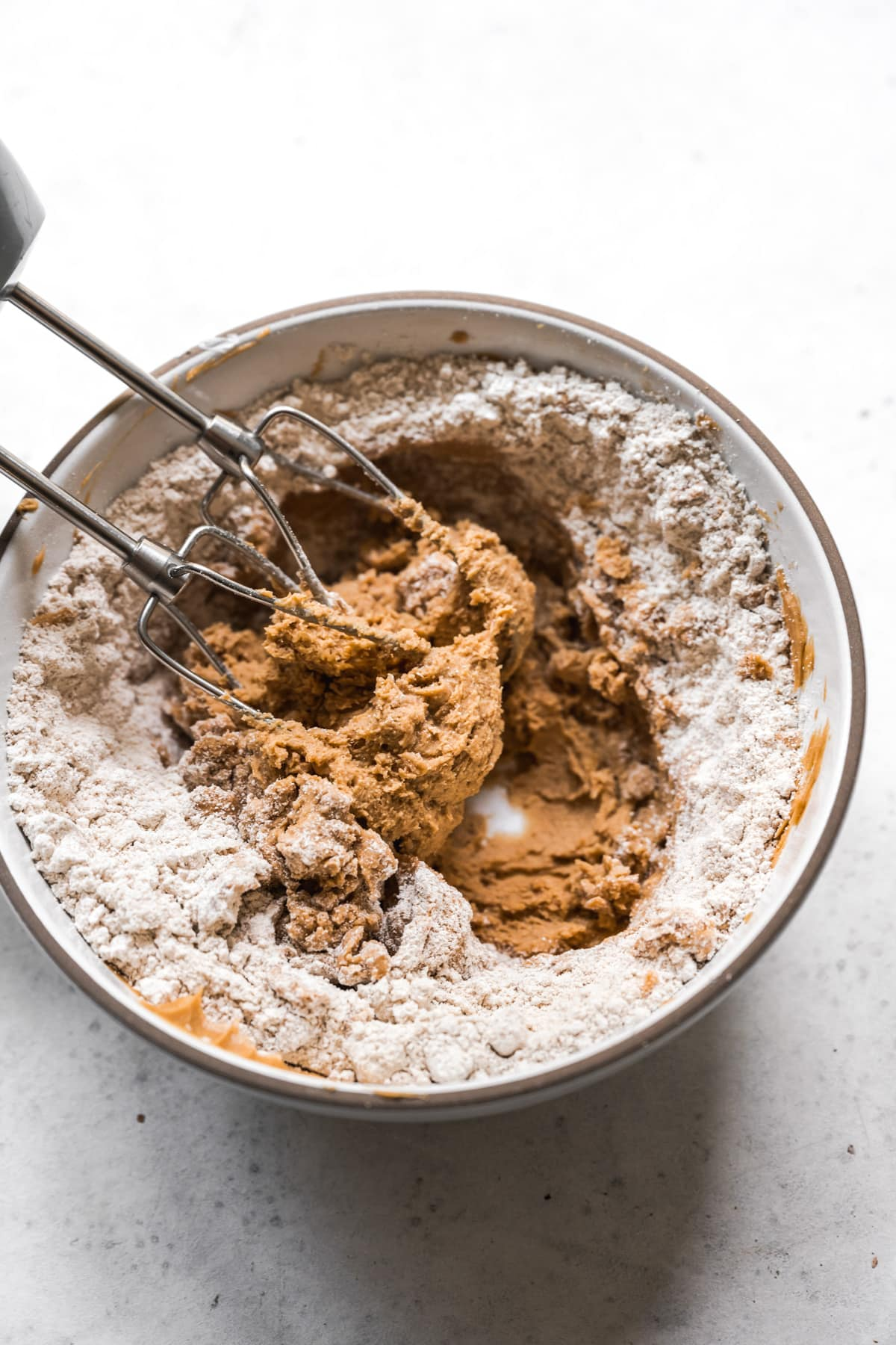 flour and peanut butter mixture being combined in mixing bowl with electric mixer.