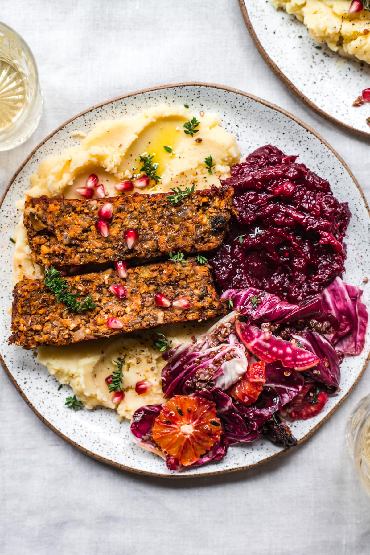 overhead view of vegan meatloaf on a white plate over mashed potatoes with cranberry sauce and salad on the side.