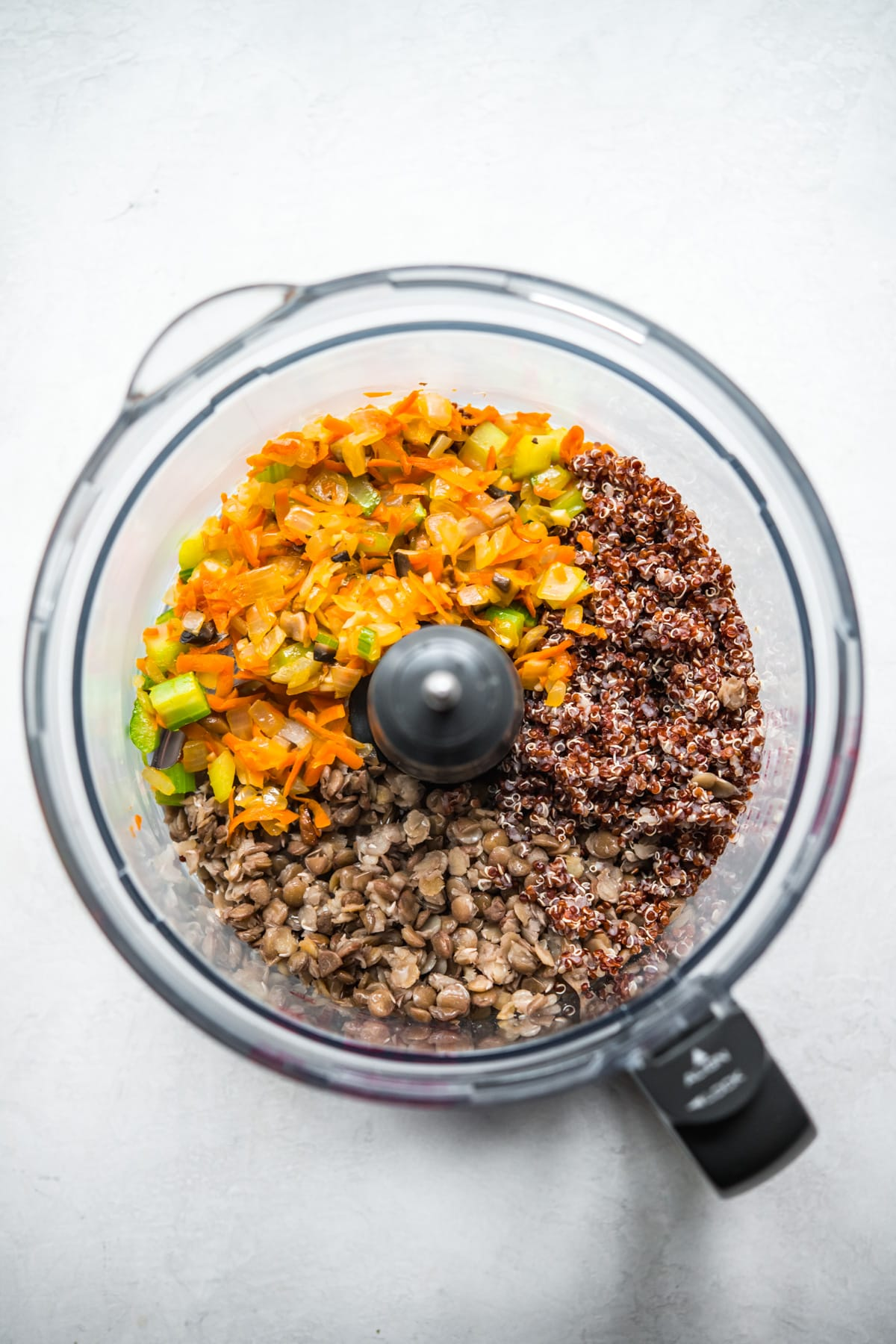 overhead view of cooked vegetables, lentils and quinoa in a food processor.