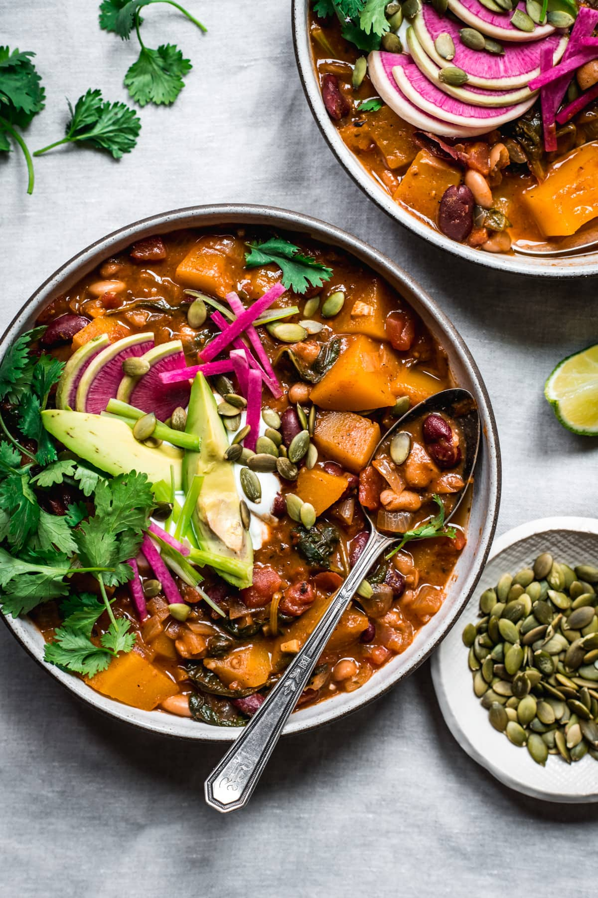 overhead view of bowl of vegan pumpkin chili topped with avocado slices, sour cream, pumpkin seeds and watermelon radish.