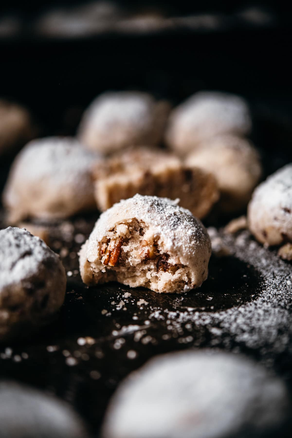 close up view of vegan pecan snowball cookie with bite taken out.