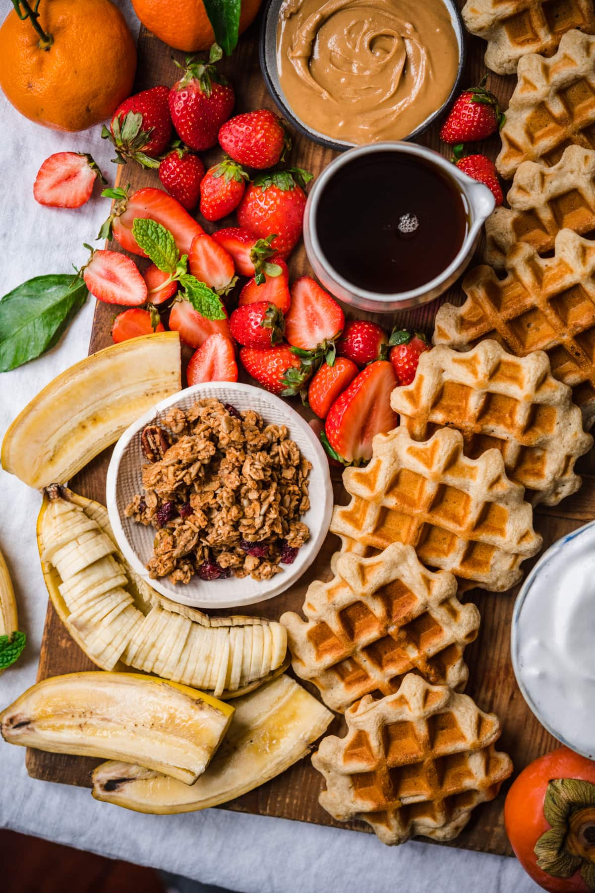 overhead view of waffle board with granola, fruit and bananas.