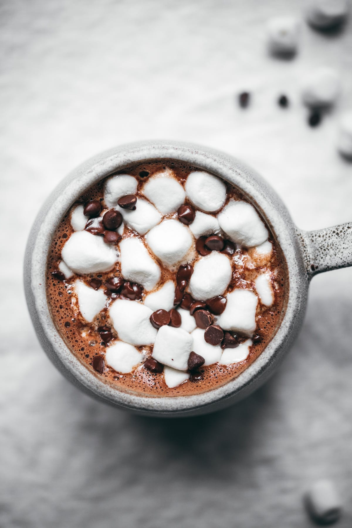 close up view of vegan hot chocolate with mini marshmallows and chocolate chips.