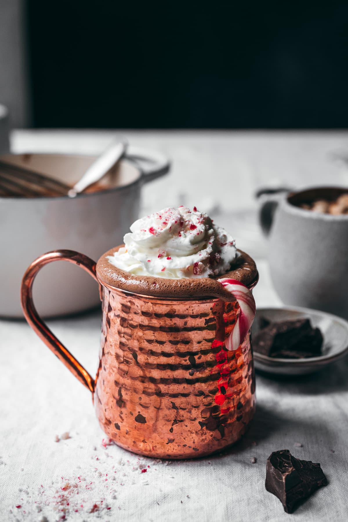 side view of vegan peppermint hot chocolate in copper mug topped with whipped cream and candy canes.