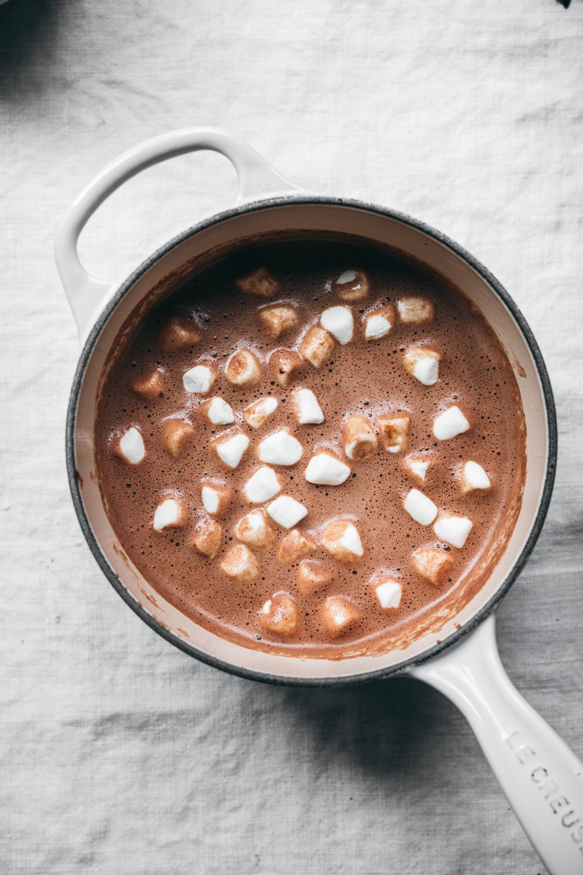vegan hot chocolate in white saucepan topped with mini marshmallows.