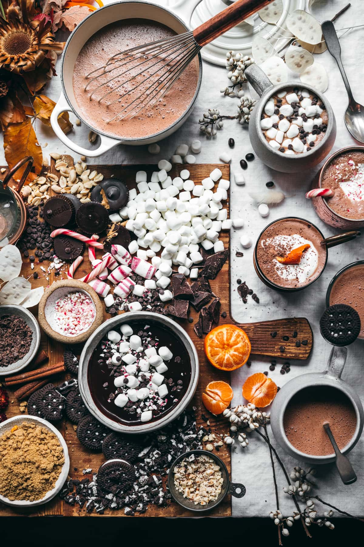overhead view of hot cocoa board with lots of toppings and mugs of hot chocolate.