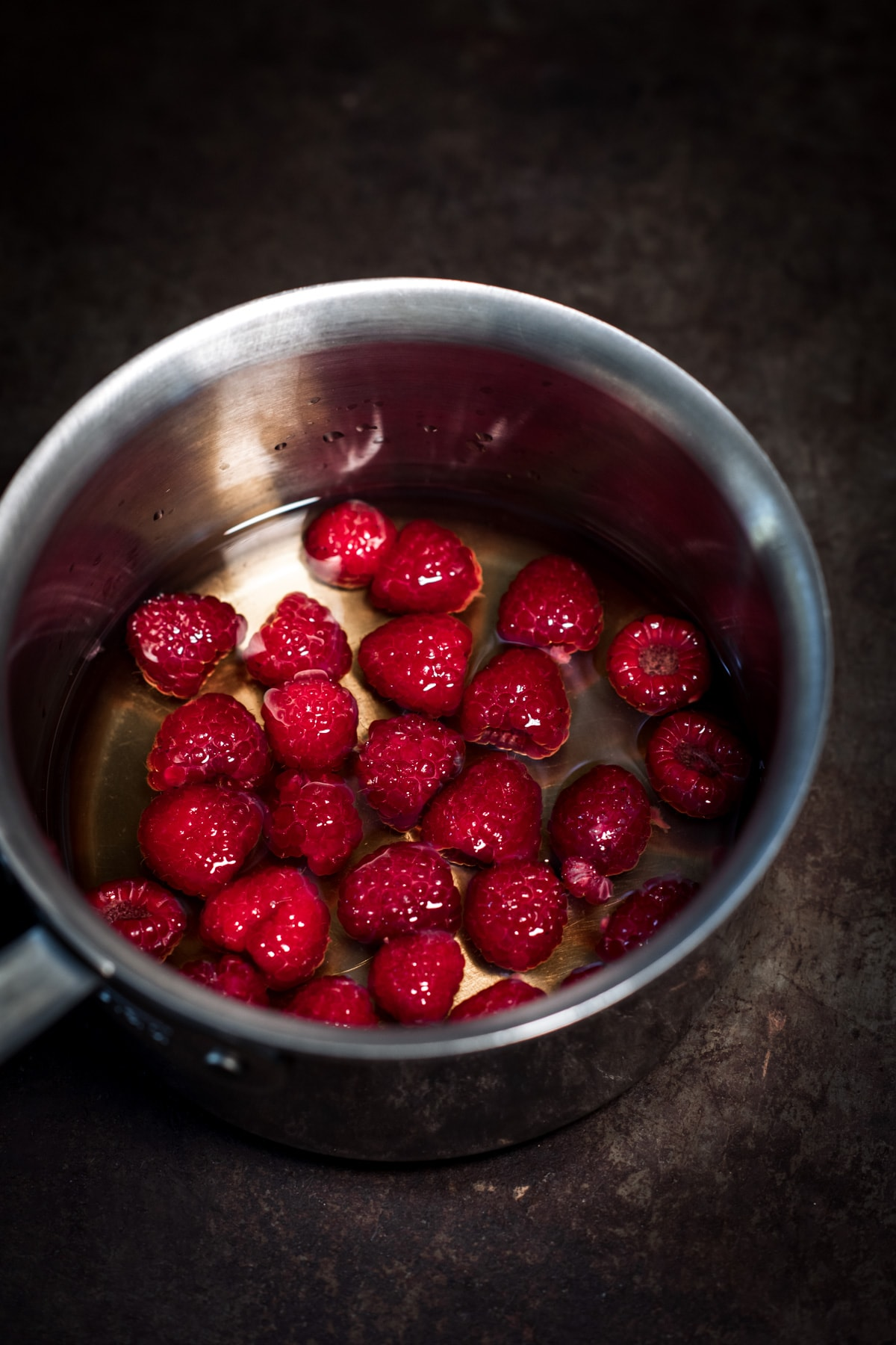 close up view of raspberry simple syrup in pot.