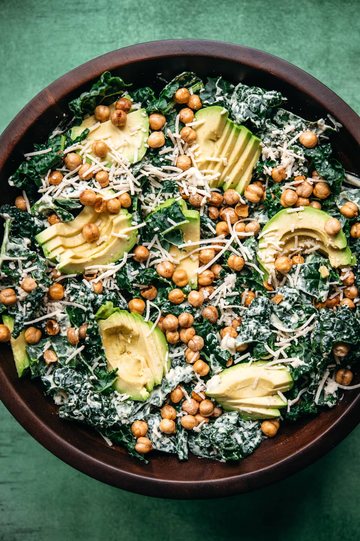 overhead view of vegan kale caesar salad in a large wood bowl topped with avocado and crispy chickpeas.