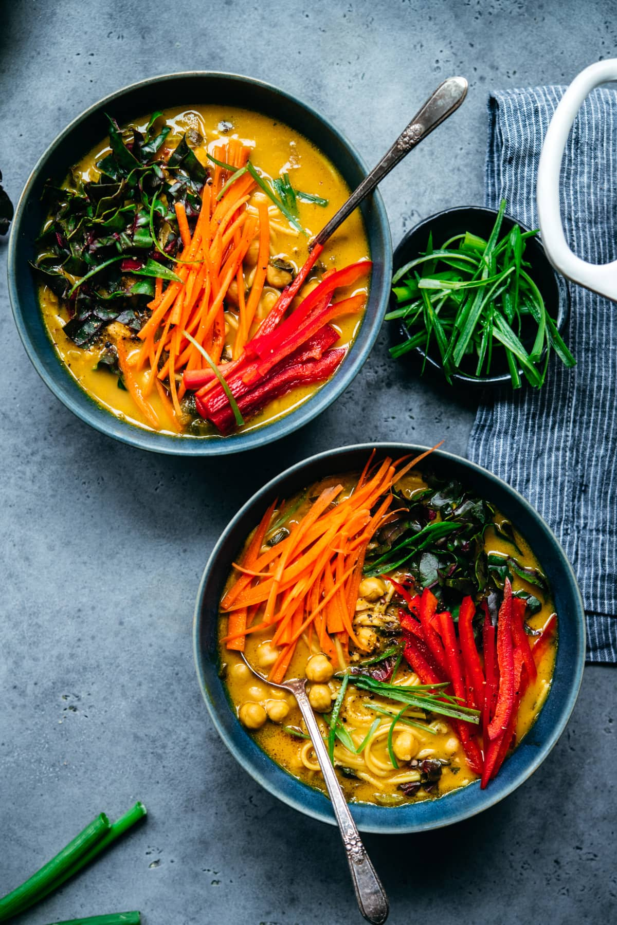 overhead view of two large bowls of chickpea noodle soup topped with fresh carrots and bell pepper.