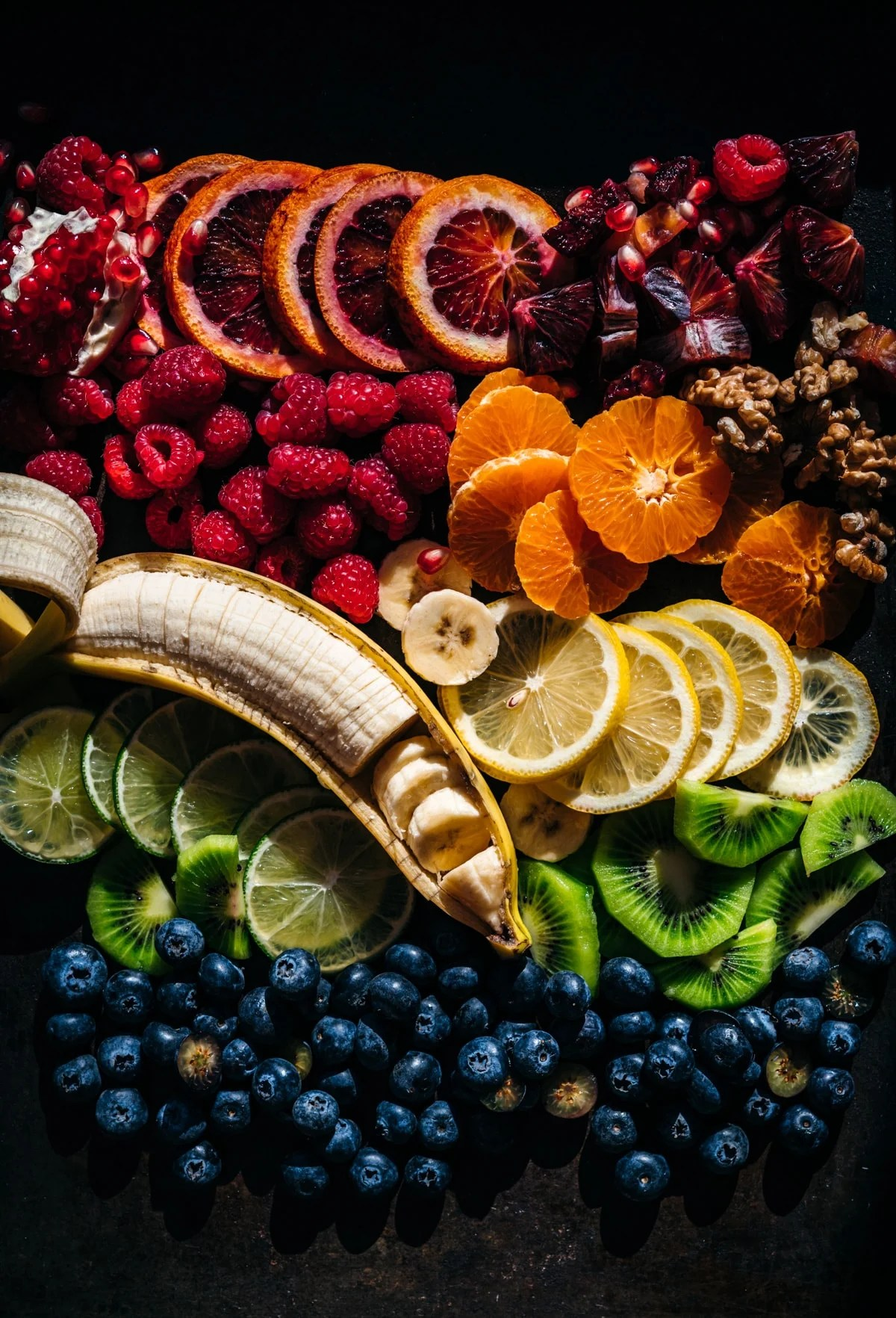 overhead view of rainbow of fresh fruits arranged on a platter.