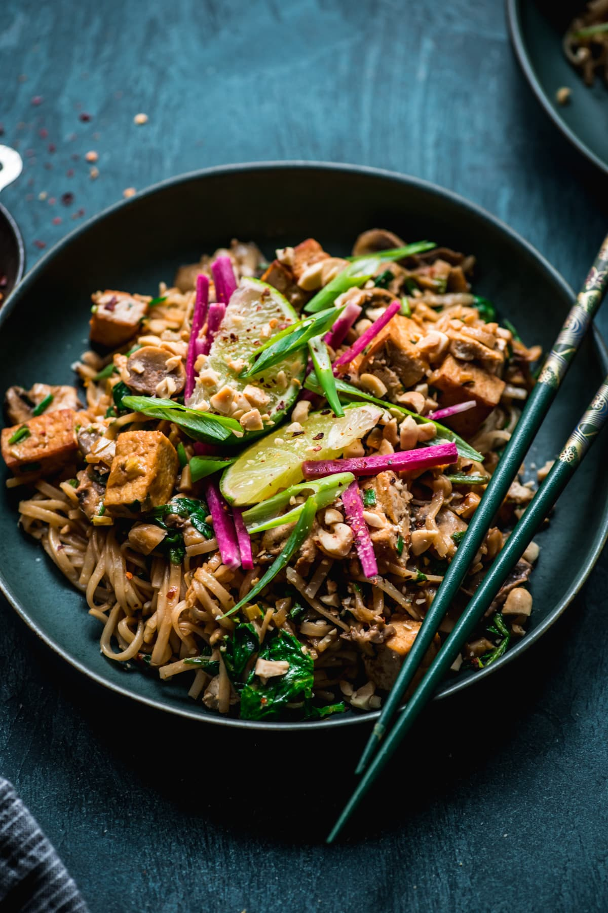 close up view of vegan tofu pad thai in a blue bowl topped with lime and radish.
