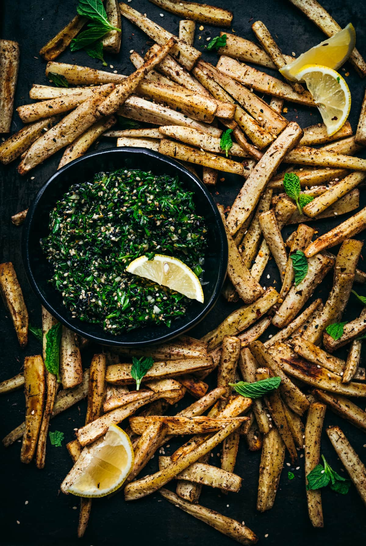 overhead view of roasted parsnips on a sheet pan with a bowl of za'atar gremolata.