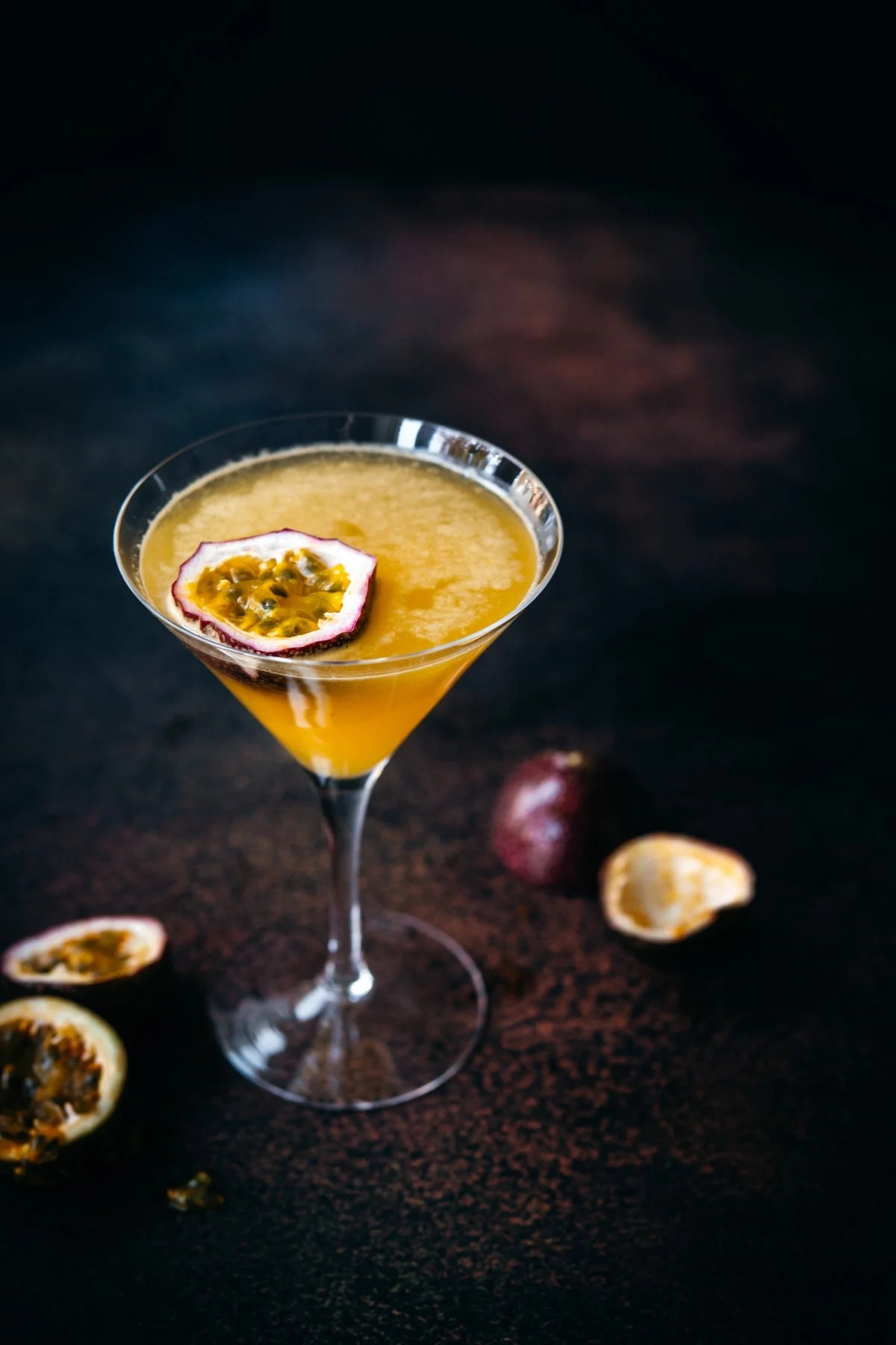 close up view of a passion fruit martini in a glass with dark backdrop.