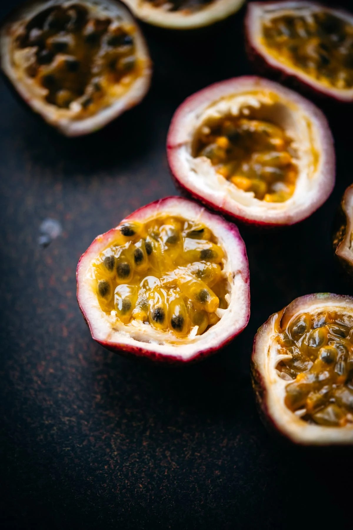close up view of a passion fruit sliced in half.