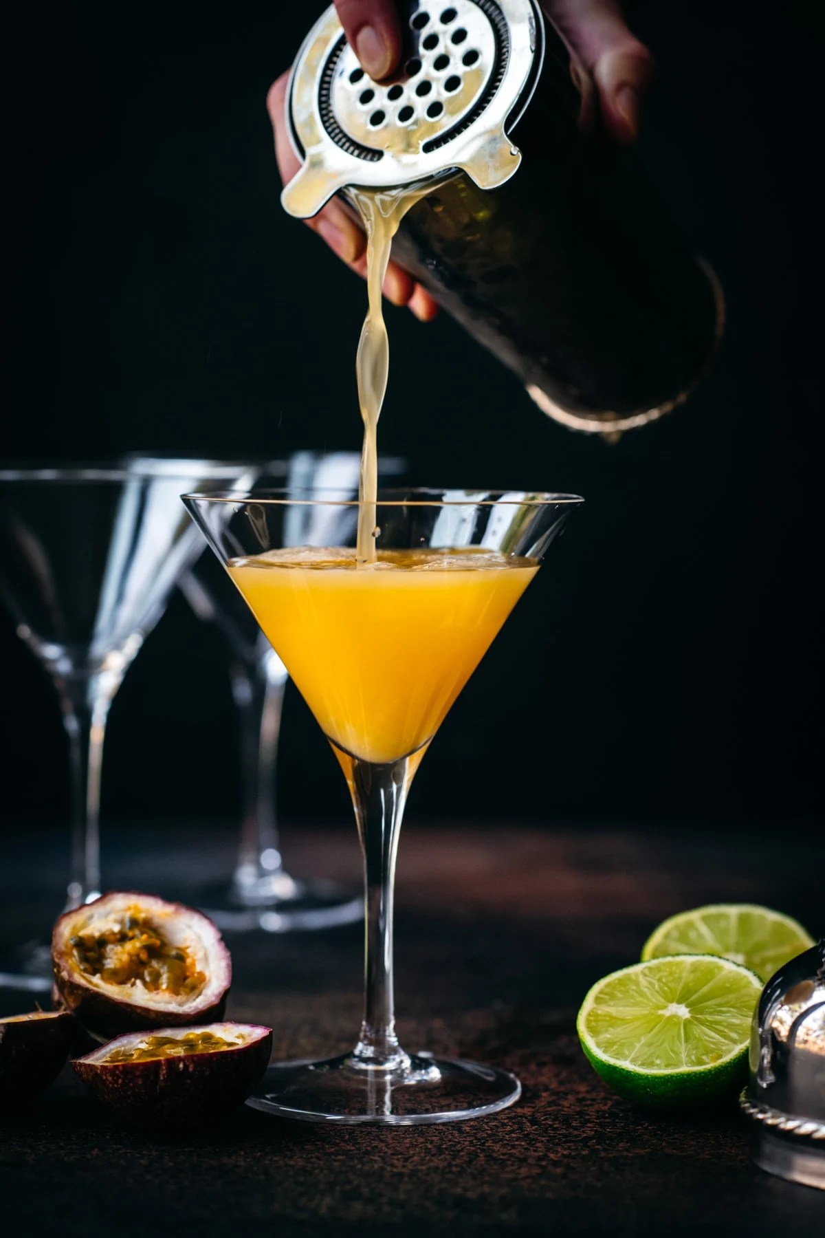 Pouring passion fruit martini into a glass from cocktail shaker.