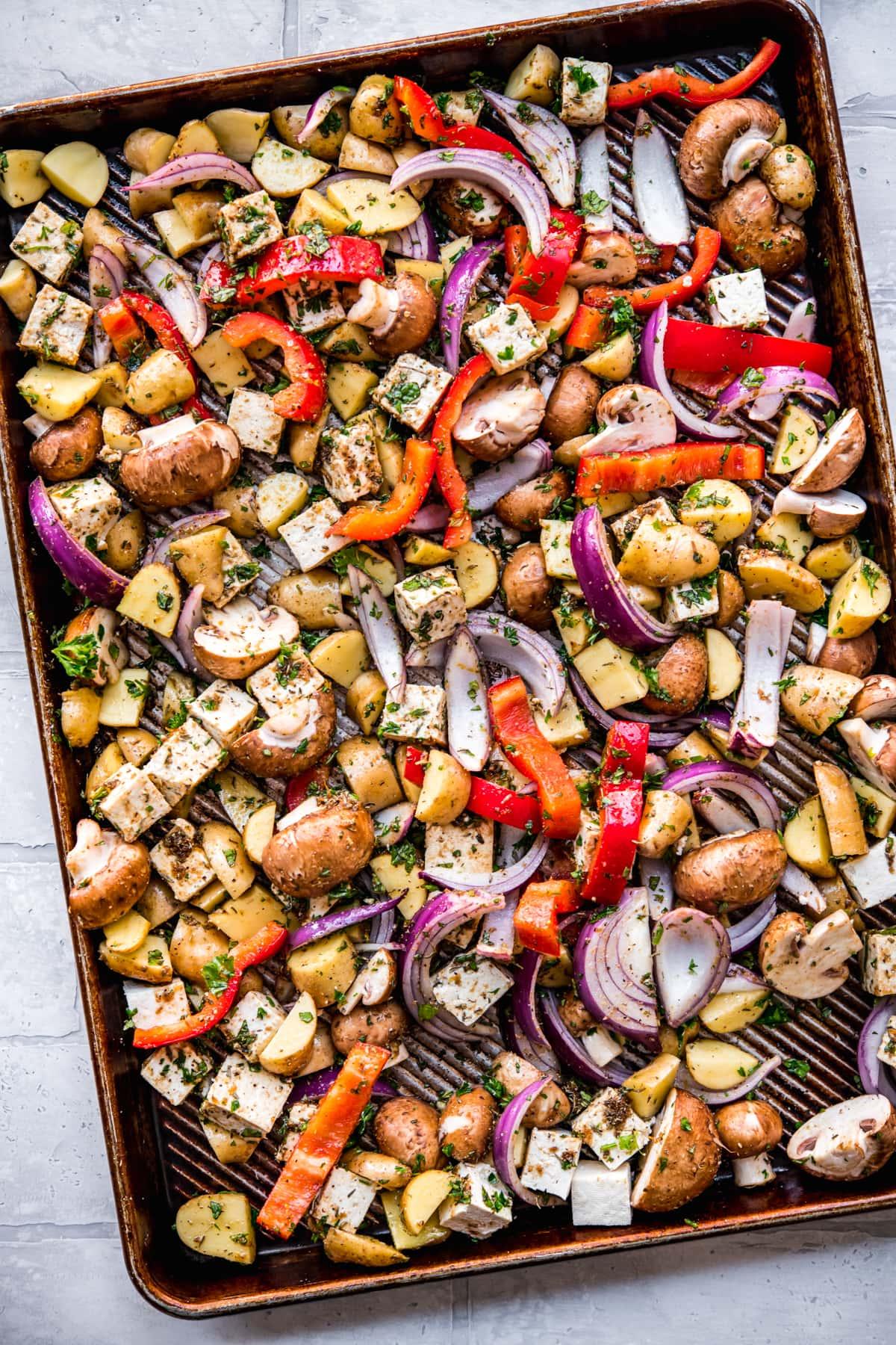 overhead view of vegan mediterranean sheet pan dinner with tofu and vegetables before roasting.