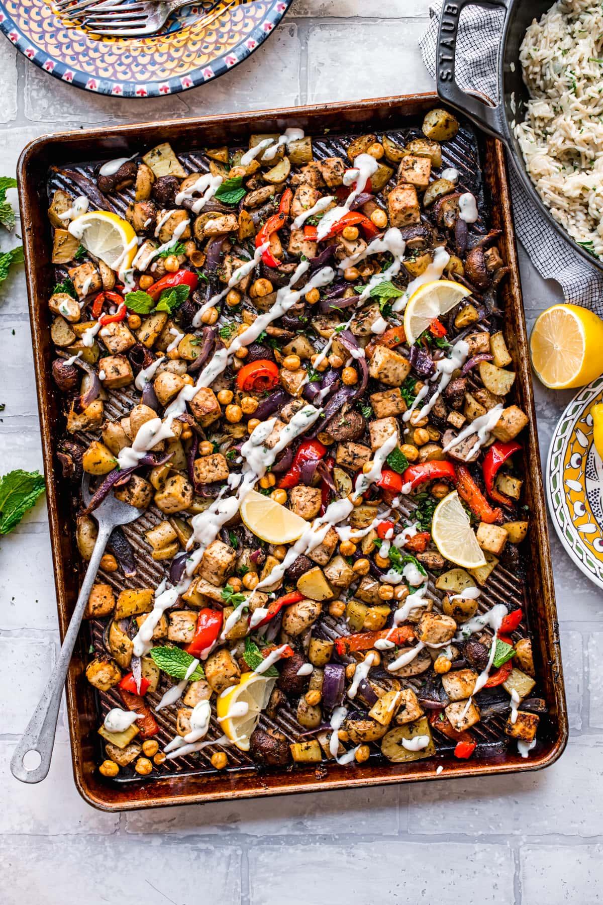 overhead view of vegan mediterranean sheet pan dinner with tofu, chickpeas, vegetables and tahini yogurt drizzle.