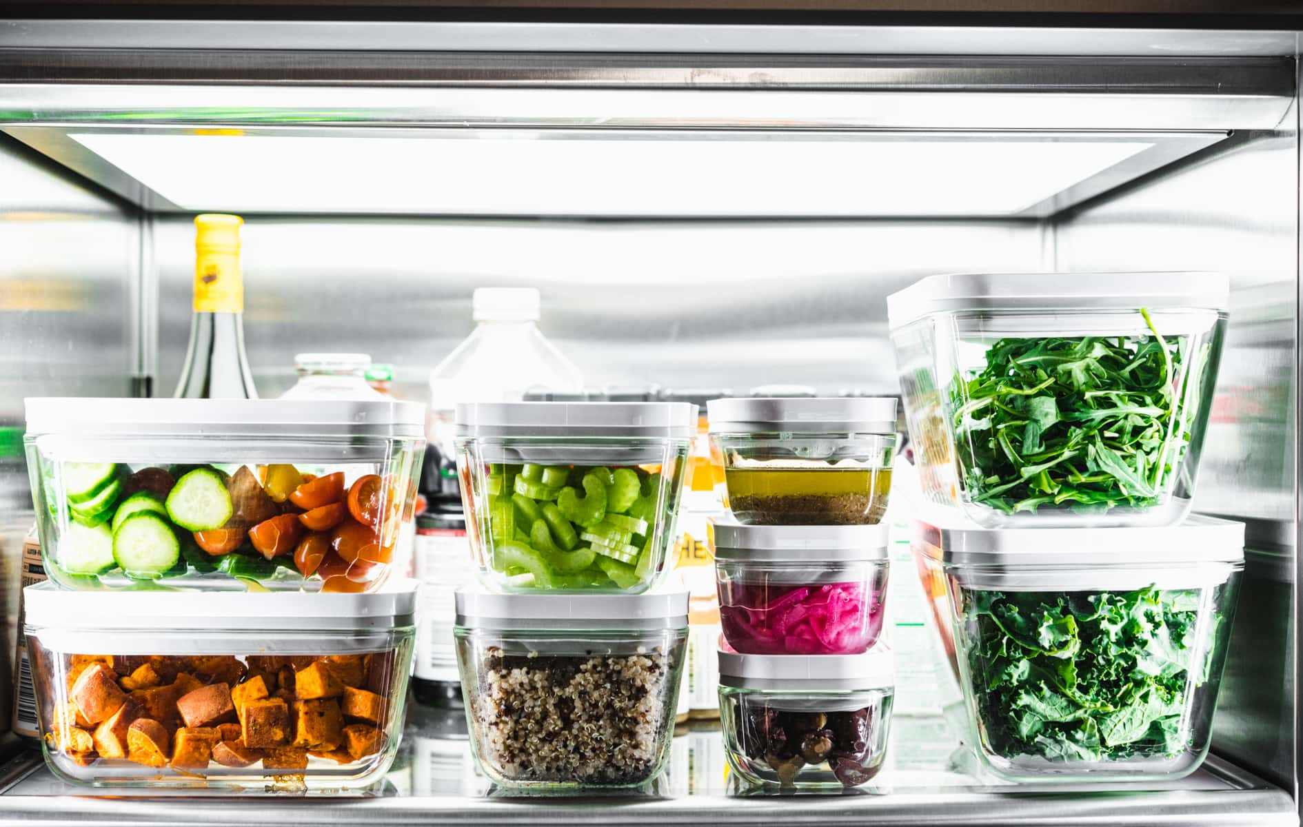 multiple meal prep containers stacked in a refrigerator filled with salad ingredients.