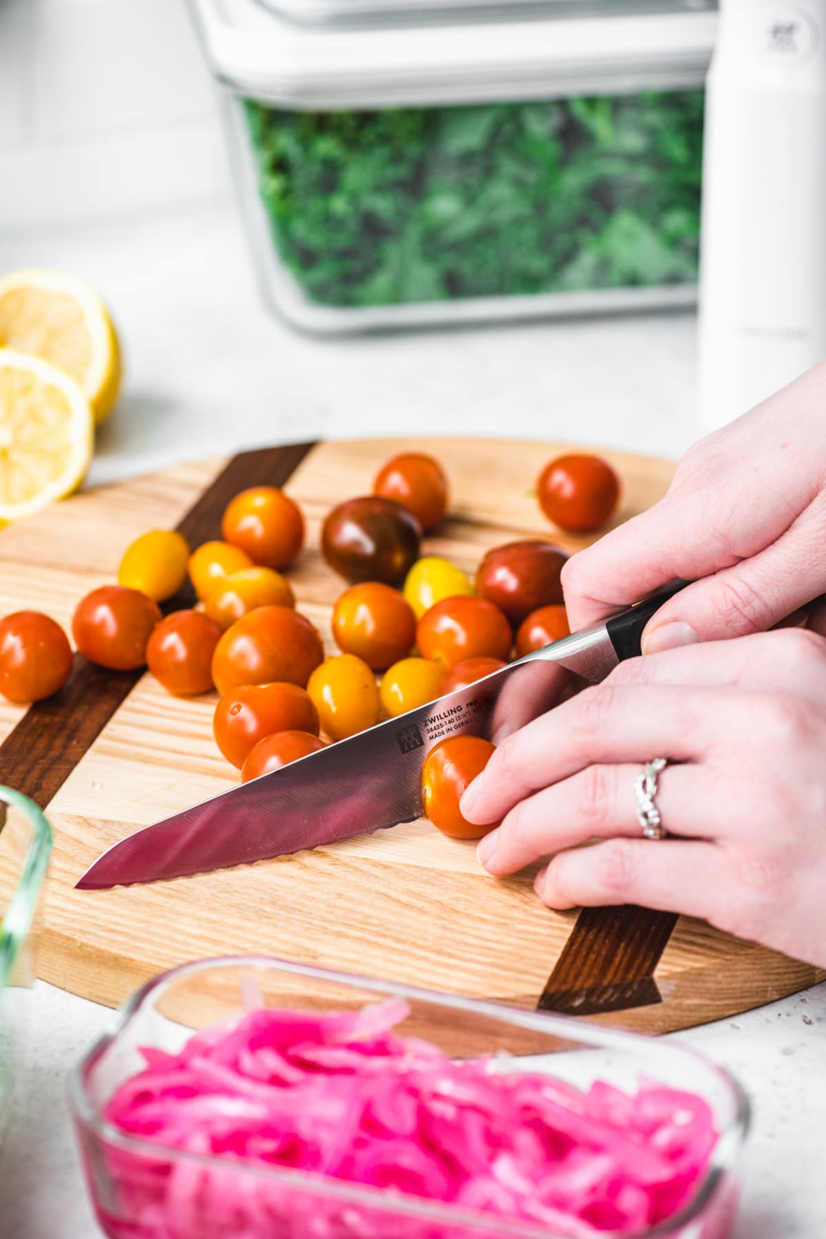 close up of person slicing cherry tomatoes in half.