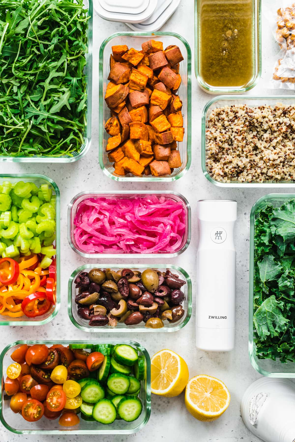 overhead view of several meal prep containers filled with various salad ingredients, like roasted and raw sliced vegetables, greens, quinoa, etc.
