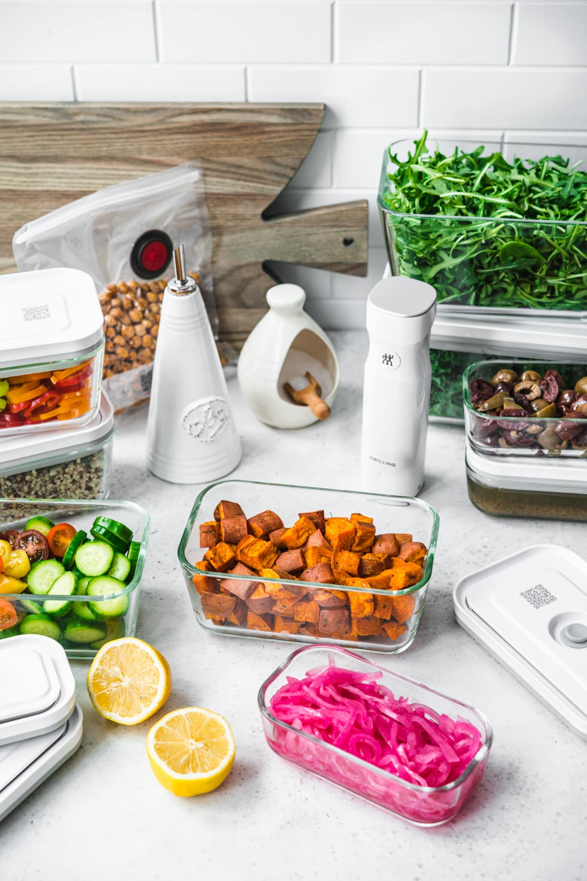 side view of several meal prep containers filled with salad ingredients, like greens, roasted sweet potato and fresh vegetables.