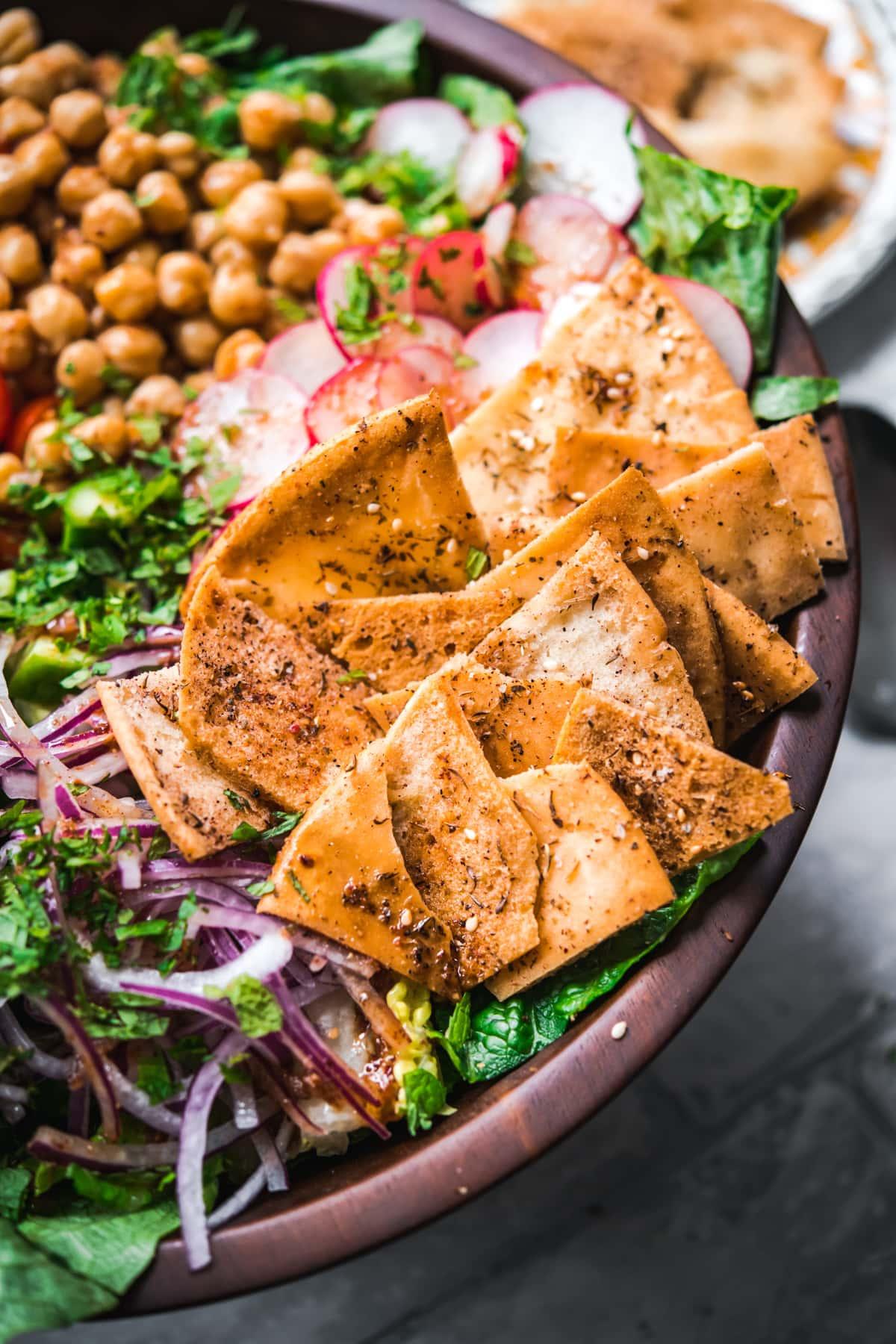 close up view of za'atar spiced pita chips on fattoush salad.