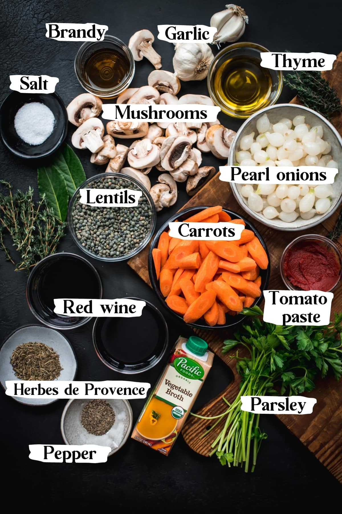 overhead view of ingredients for vegan coq au vin including mushrooms, carrots, pearl onions and wine.