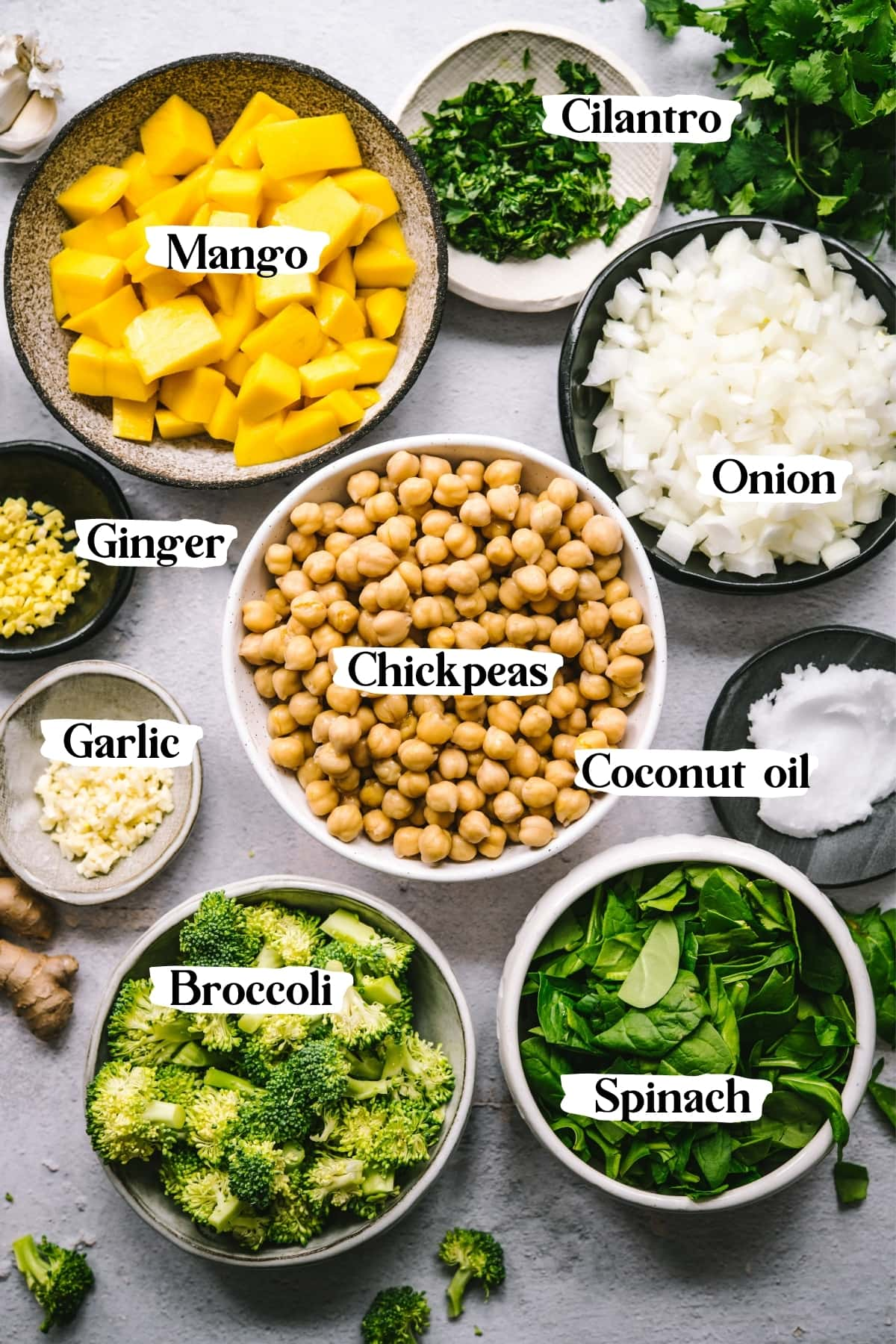 overhead view of ingredients for mango chickpea curry, including chickpeas, onion, coconut oil, cilantro, mango and more.