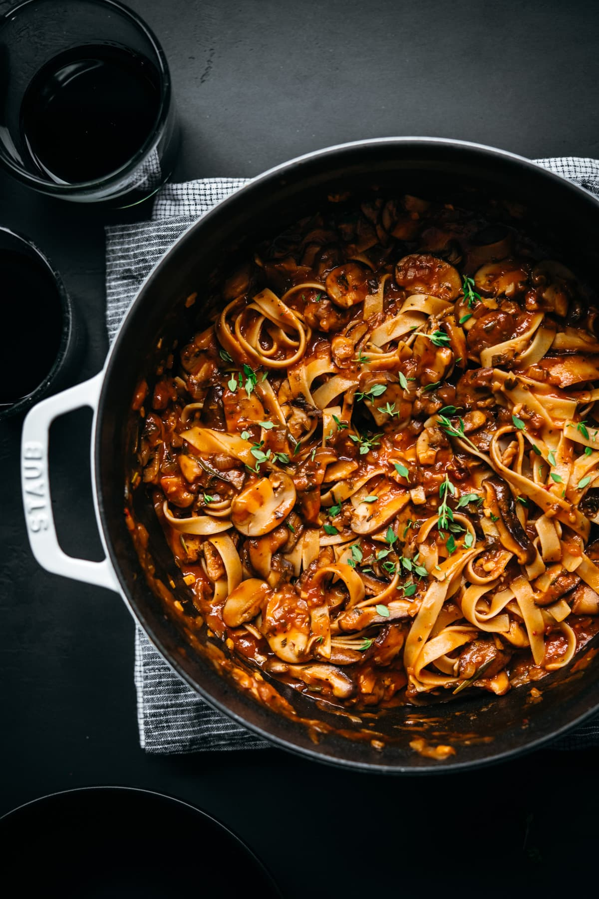 overhead view of vegan mushroom ragu over pasta in a large white dutch oven.