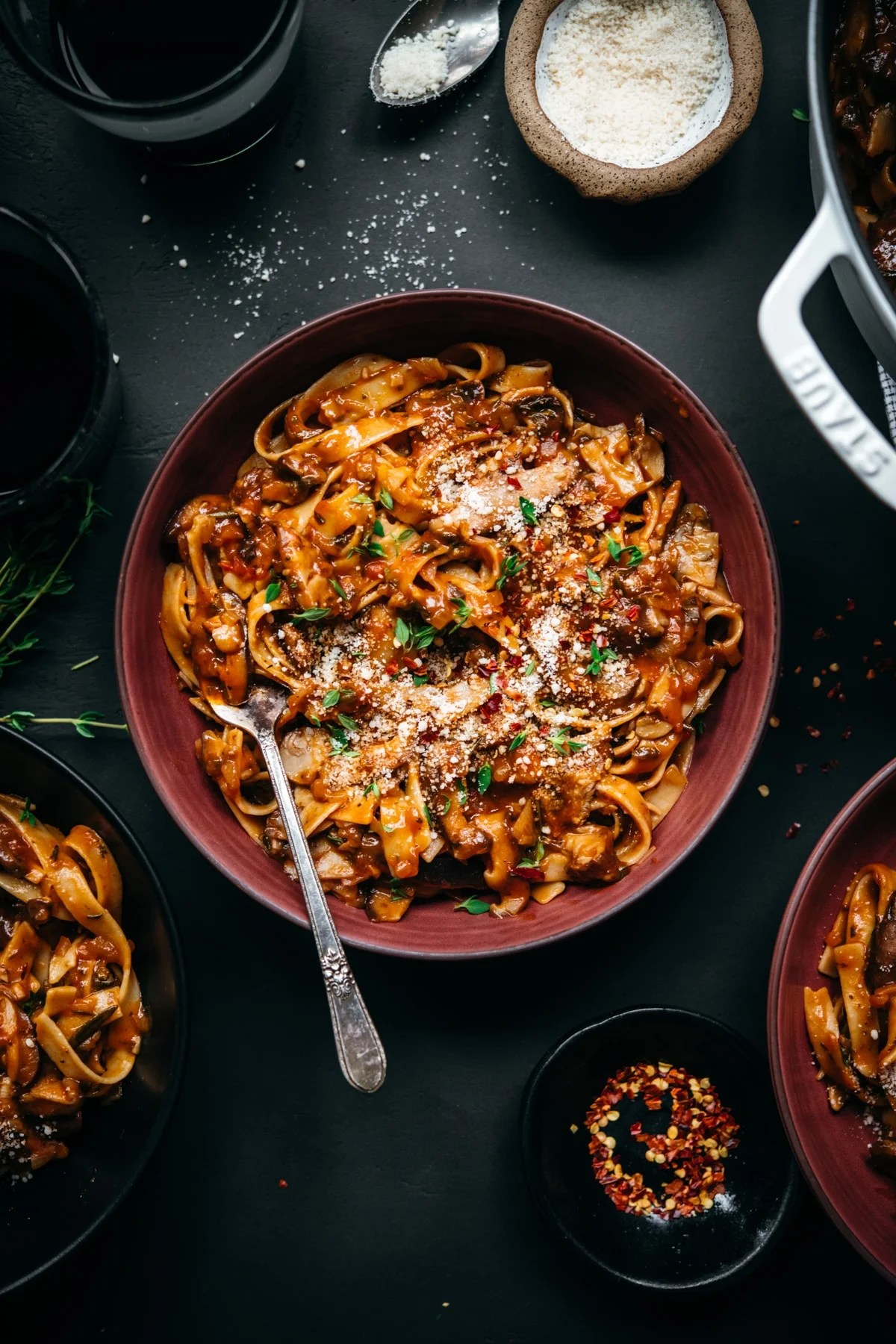 overhead view of vegan mushroom ragu over pasta in a red bowl.