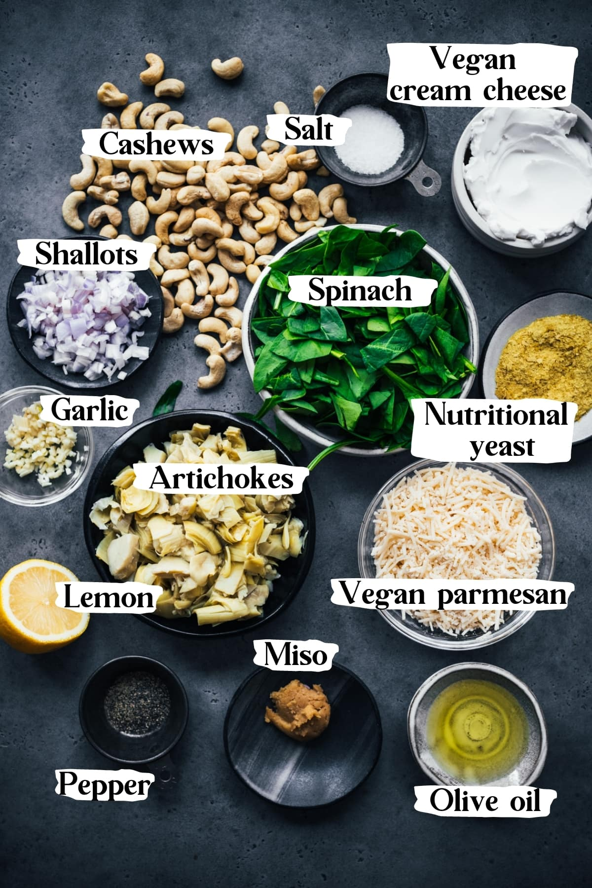 overhead view of ingredients for vegan spinach artichoke dip, including cashews, vegan cheese, spinach, artichokes, shallots.