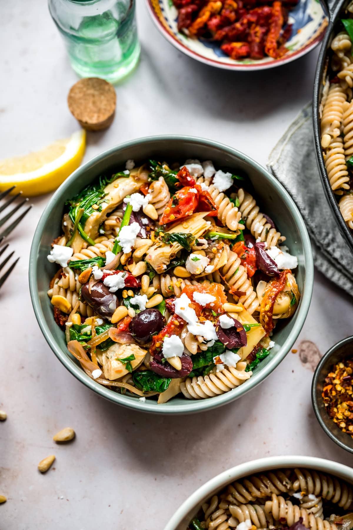 overhead view of vegan greek pasta in a blue bowl.