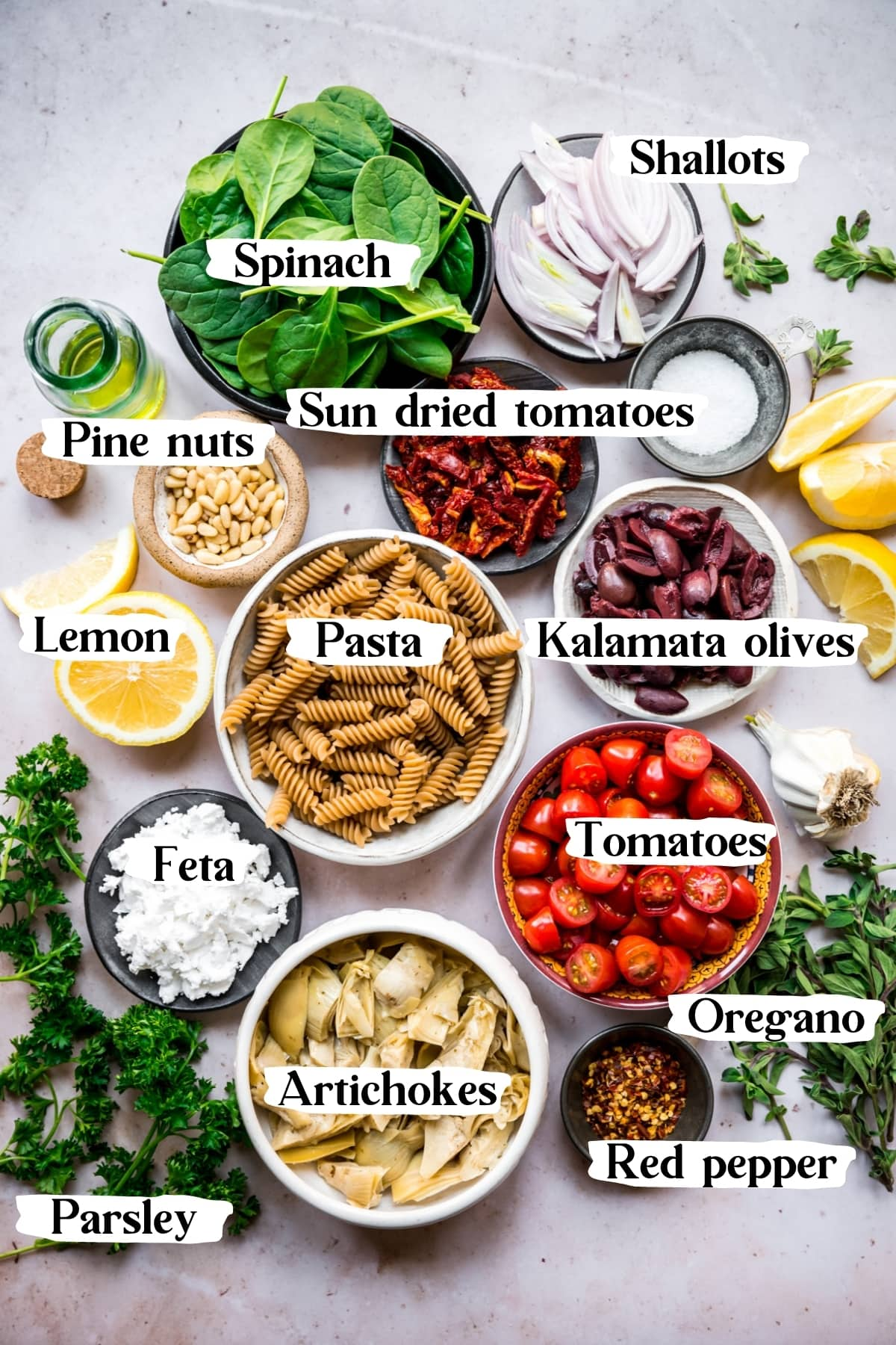 overhead view of ingredients for greek pasta in small bowls.