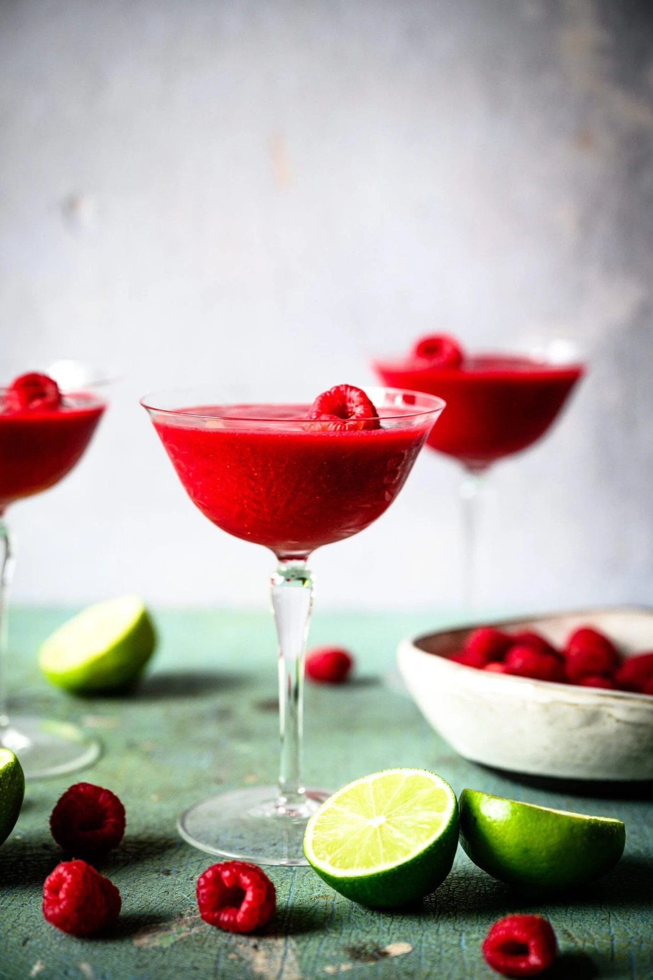 side view of frozen raspberry daiquiri in coupe glass with fresh raspberries and lime slices.
