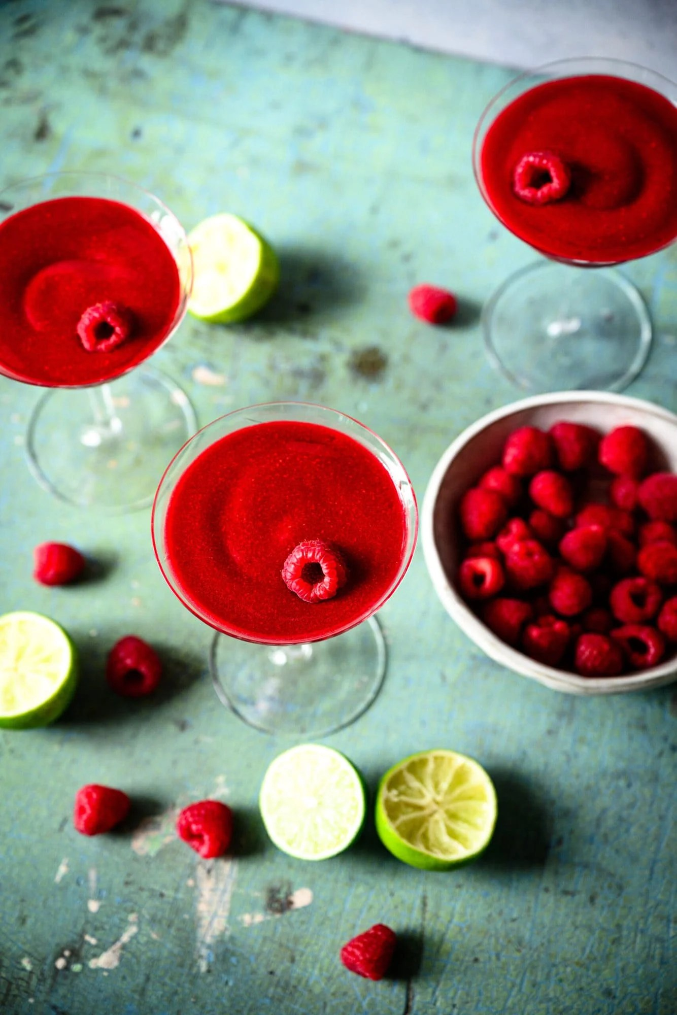 overhead view of frozen raspberry daiquiri in coupe glass with fresh raspberries and lime slices.