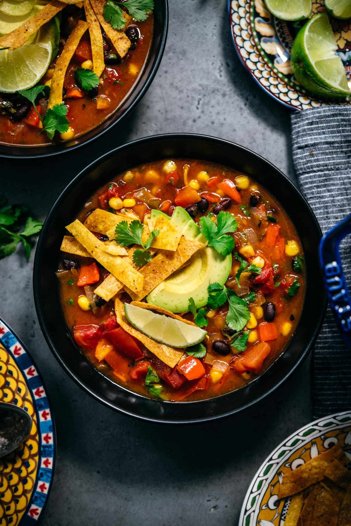 overhead view of vegan tortilla soup in black bowls topped with avocado, tortilla strips and lime.